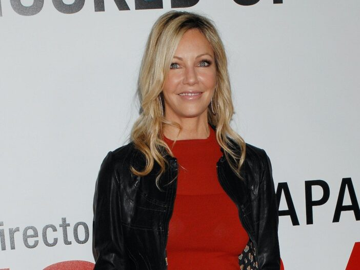 Heather Locklear smiling in a red dress and black jacket against a white background