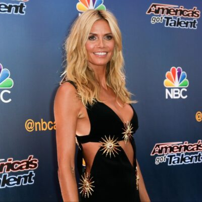 Heidi Klum wearing a black dress with golden details on the red carpet at an America's Got Talent event