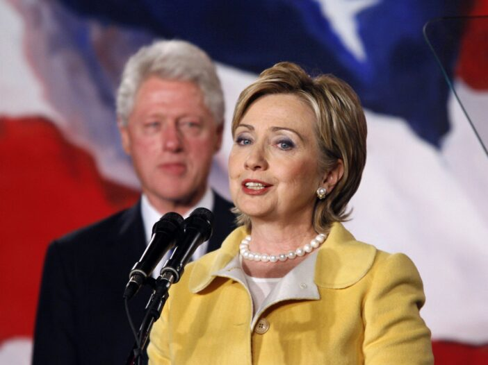 Hillary Clinton in the foreground wearing a yellow pantsuit, Bill Clinton in the background looking on as Hillary speaks at a podium.