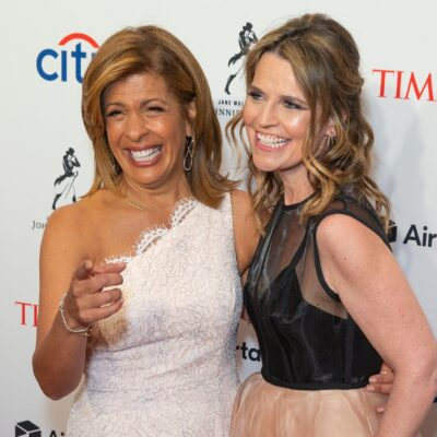 Hoda Kotb, in white, grins and points as she poses with Savannah Guthrie, in black and cream dress