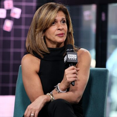 Hoda Kotb wearing all black sits in a green chair on a sound stage holding a microphone