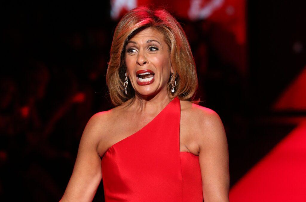 Hoda Kotb wears a red dress as she walks down a catwalk