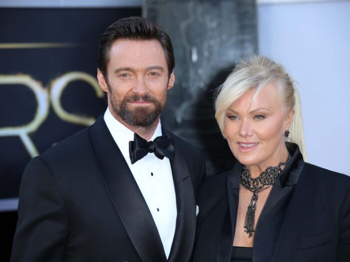 Hugh Jackman smiling in a tuxedo with wife Deborra Lee Furness in a black outfit
