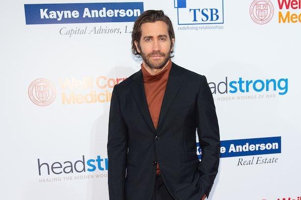 Jake Gyllenhaal in a black jacket and orange turtleneck