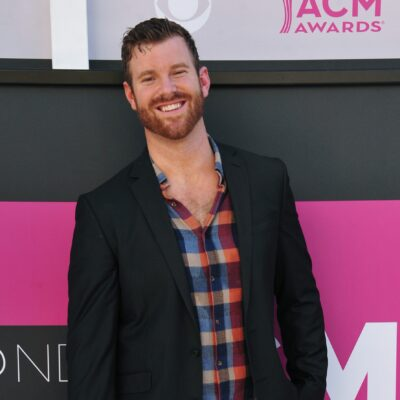 James Taylor wearing a black jacket over a plaid shirt stands before a black and pink background
