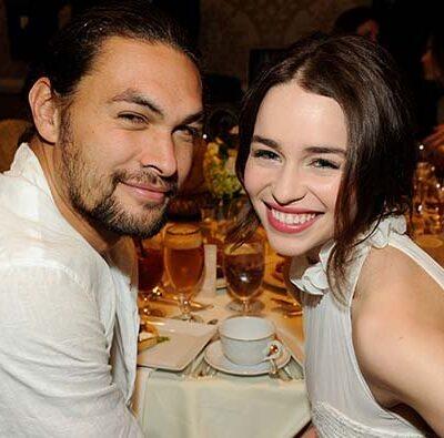 jason Momoa and Emilia Clarke pose together at a dinner table.