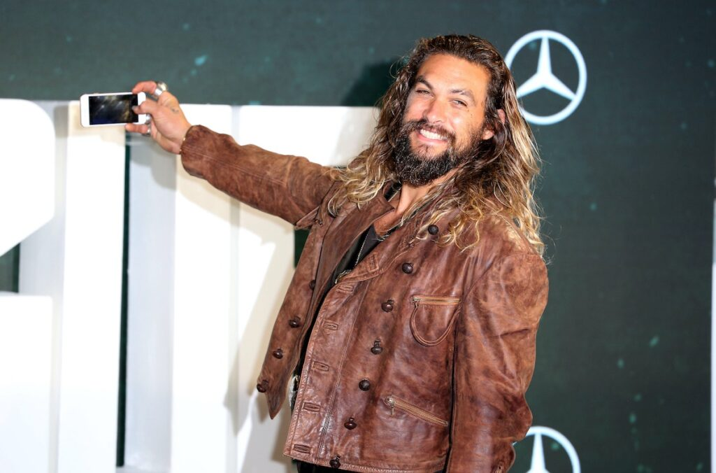 Jason Momoa smiling in a leather jacket taking a selfie
