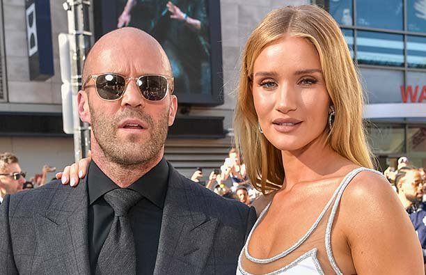 ason Statham in a suit and sunglasses and Rosie Huntington-Whiteley in a white dress on the red carp