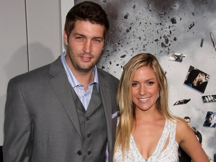 Jay Cutler in a gray suit stands with Kristin Cavallari, in a white dress, at a movie premiere