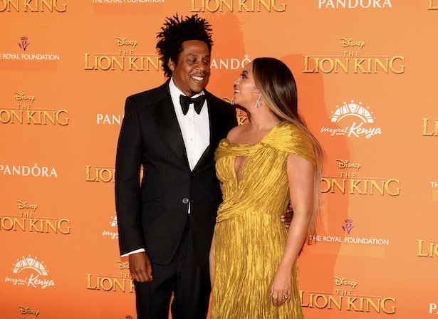 Jay Z in a tux smiles and looks at Beyonce in a yellow dress against an orange background