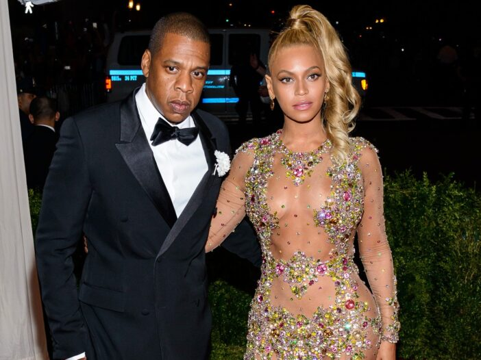 Jay-Z, wearing a black tux, enters the Met Gala with Beyonce, in bejeweled dress
