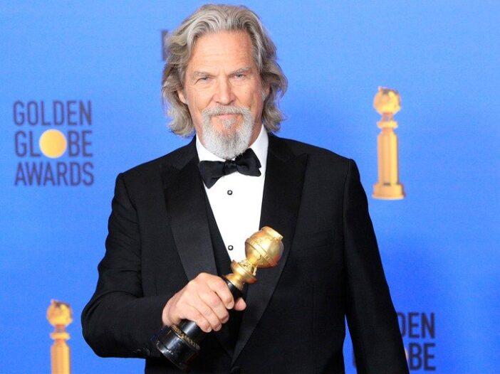 Jeff Bridges in a tuxedo, holding a Golden Globe award.