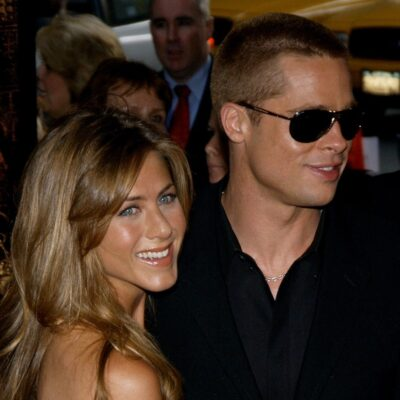 Jennifer Aniston and Brad Pitt hugging and smiling at the US Premiere of _Troy_ in 2004.