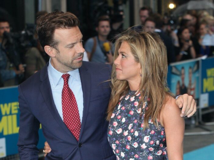 Jennifer Aniston in a black and floral dress smiling at Jason Sudeikis in a suit