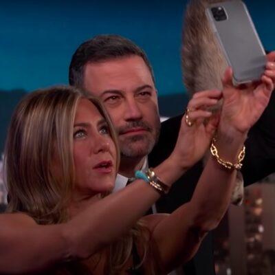 Jennifer Aniston in a black dress taking a selfie with Jimmy Kimmel in a suit holding a ferret