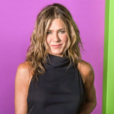 Jennifer Aniston smiling in a black dress against a pink and green background