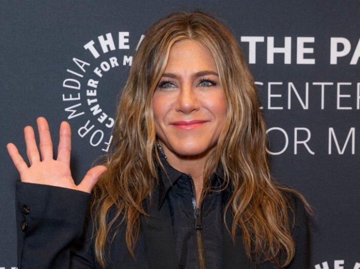 Jennifer Aniston waving, wearing a dark top.