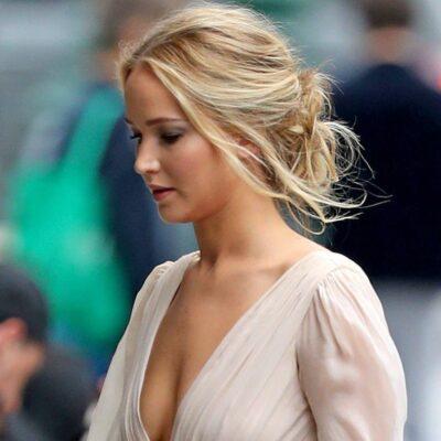 Jennifer Lawrence in a white dress walks down the street looking down