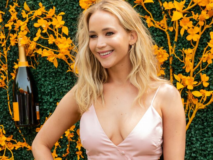 Jennifer Lawrence smiling in a pink dress and her hand on her right hip.