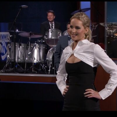 Jennifer Lawrence standing in front of Jimmy Kimmel's band in a black and white dress.