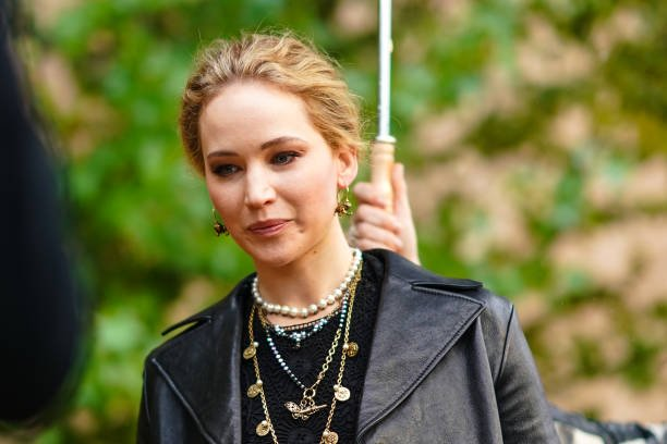Jennifer Lawrence wears earrings, necklaces, a black lace crop top, a black leather jacket, outside