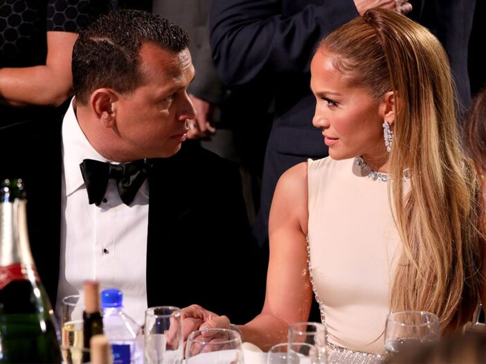 Jennifer Lopez and Alex Rodriguez holding hands at a dinner table.