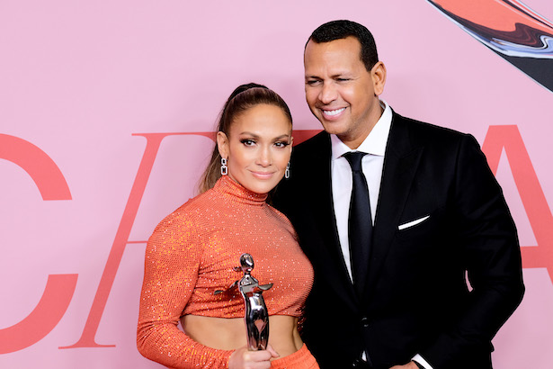 Jennifer Lopez smiles and holds her Fashion Icon Award in an organge dress with a smiling Alex Rodri
