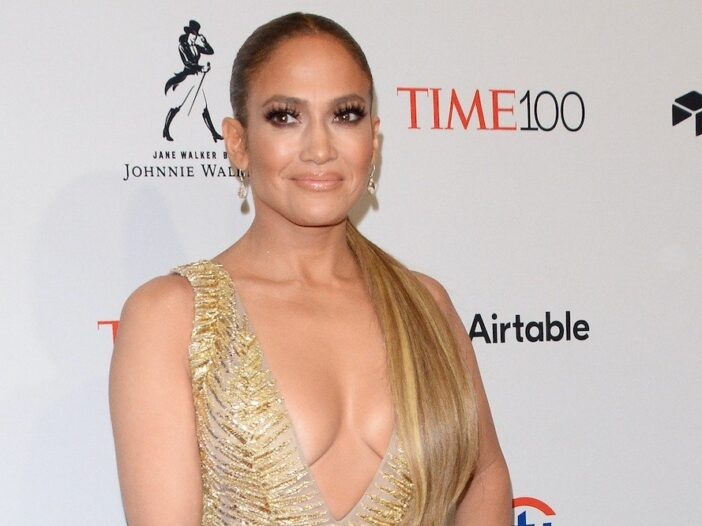 Jennifer Lopez smiling in a gold dress against a white background