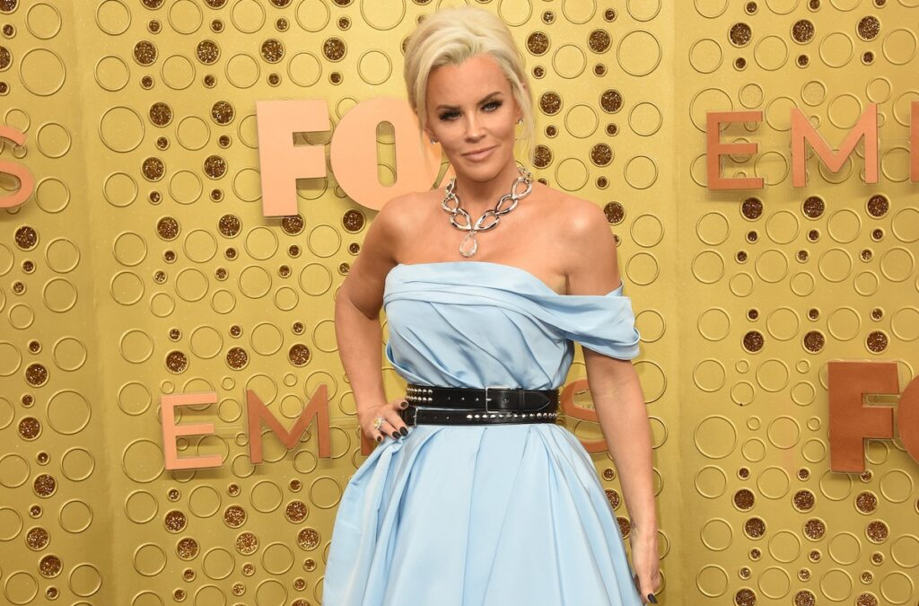 Jenny McCarthy smiling in a blue dress against a yellow background