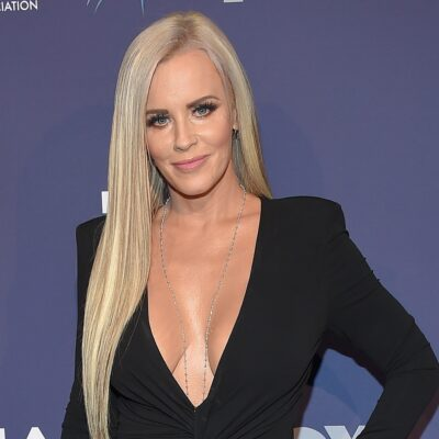 Jenny McCarthy smiling with her hand on her hip.