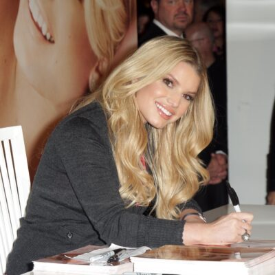 Jessica Simpson at a signing event at Macy's wearing a heather gray sweater.