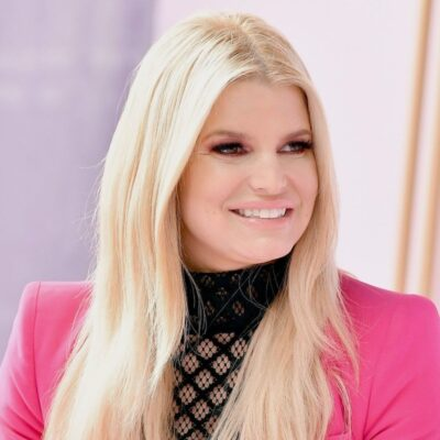 Jessica Simpson smiles to her left dressed in a black top and pink jacket