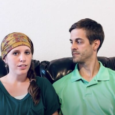 Jill and Derick Dillard sit together on a couch, each wearing green.