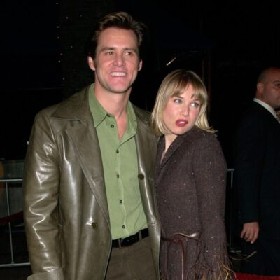 Jim Carrey wearing a brown suit, green shirt on the red carpet with Renee Zellweger, also in brown