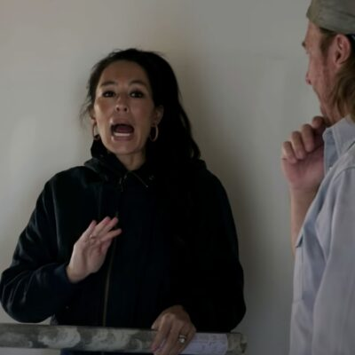 Joanna Gaines, in a black hoodie, discusses changes to a home with husband Chip Gaines, in blue