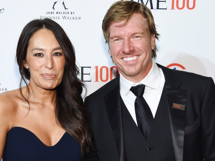 Joanna Gaines smiles in a blue dress next to Chip Gaines in a black suit and tie
