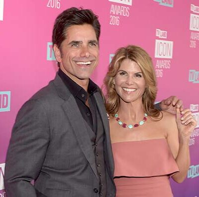 John Stamos in a grey suit with his arm around Lori Loughlin in a pink dress a red carpet