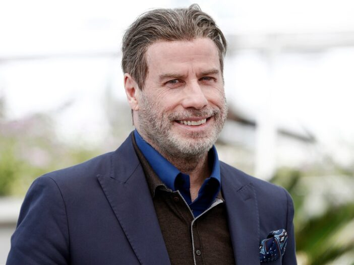 John Travolta wearing a blue suit jacket on the red carpet at the Cannes Film Festival