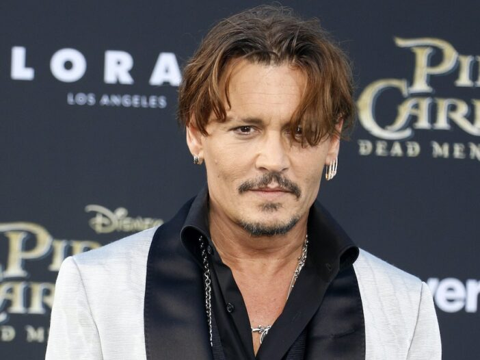 Johnny Depp in a white suit with black shirt at a red carpet event for Pirates of the Caribbean