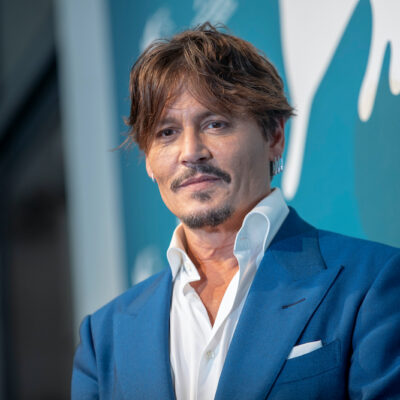Johnny Depp smiling in a blue suit and white shirt against a blue background