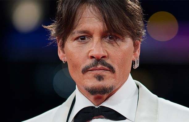 Johnny Depp, very much alive, on the red carpet in a white suit, September.