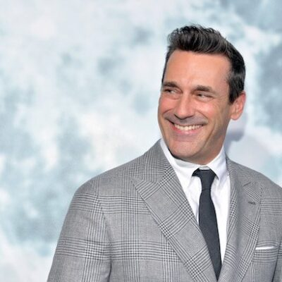 Jon Hamm smiles in a grey suit, white shirt and black tie on a white background