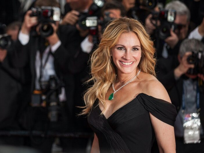 Julia Roberts smiling in a black dress on the red carpet in front of photographers