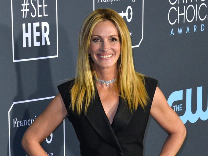 Julia Roberts smiling in a black outfit with a silver necklace