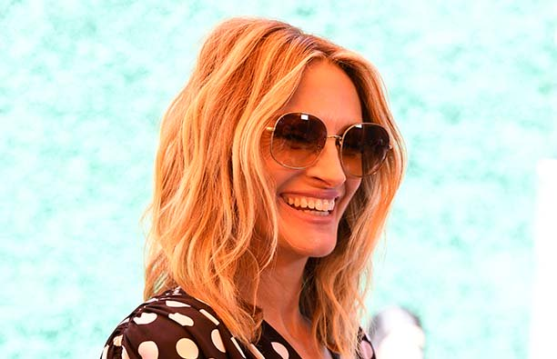 Julia Roberts smiling in sunglass in front of a teal background