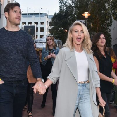 Julianne Hough wearing blue jeans, a white shirt, and a gray coat walking with Brooks Laich, who's w