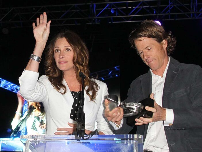 Julie Roberts holding her arm at at a dinner table next to Danny Moder looking down at an award.
