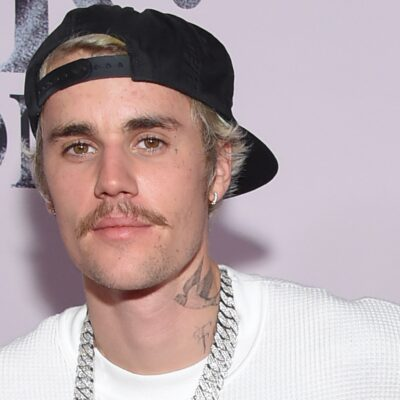 Justin Bieber wears a white top with a glittering silver necklace against a pale pink background