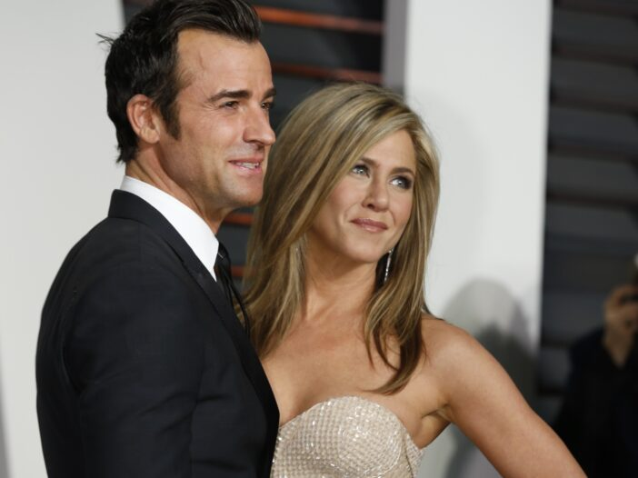 Justin Theroux on the left in a tuxedo, standing with Jennifer Aniston in a strapless dress.