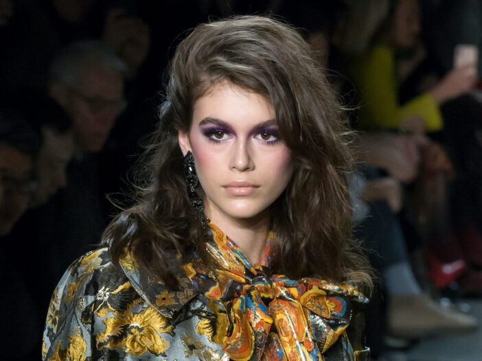 Kaia Gerber walking down the runway in a floral outfit